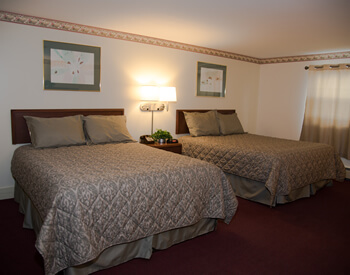 spacious room with two Queen beds each with light green bedding.