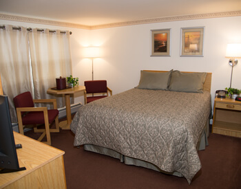Room that has two Queen size beds with two maroon colored cushioned chairs with wood trim.