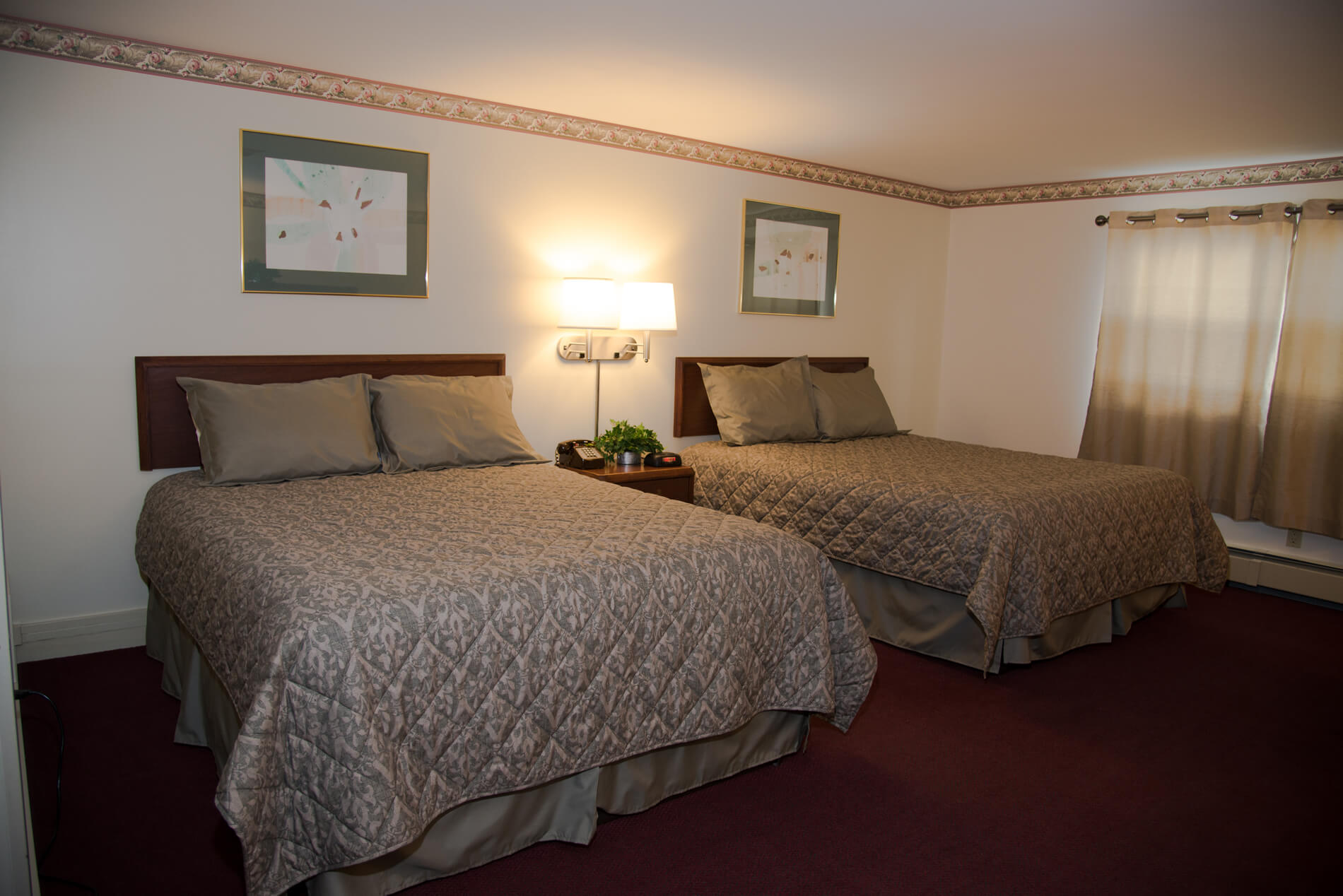 Large room in motel with two Queen size beds and cream colored curtains.