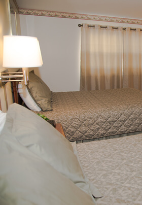 Spacious room with light green bedding with two Queen beds and flat screen TV.