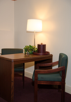 A cozy spot in a room with a table and two cushioned chairs with green fabric.