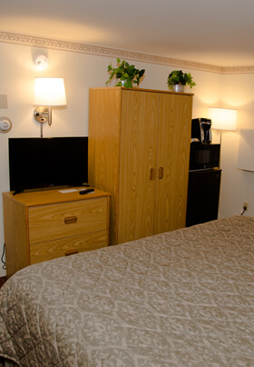 Deluxe room with King bed with green bedspread and flat screen TV.