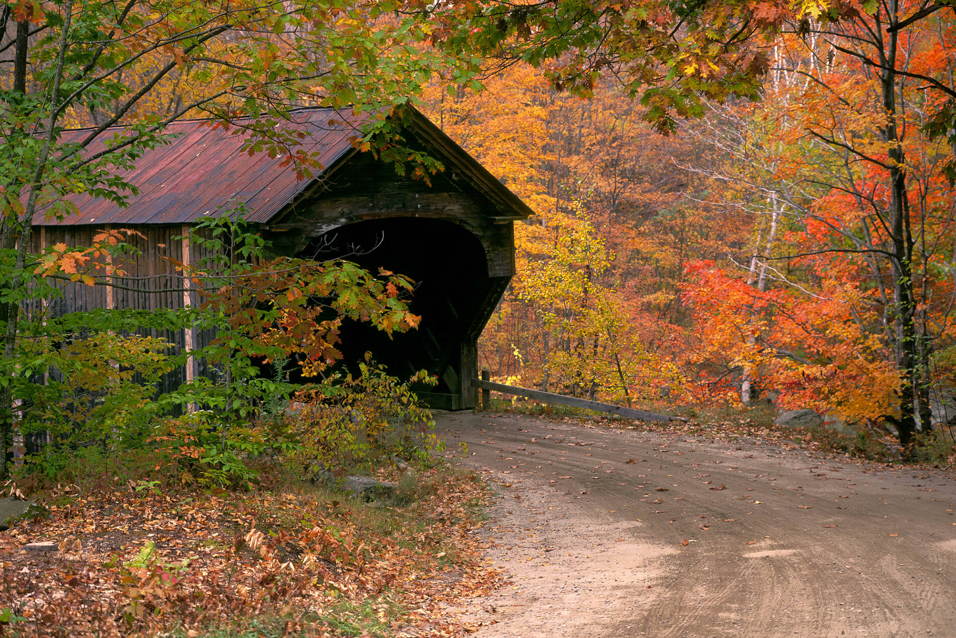 Rustic covered bridge along a dirt road in autumn with orange, green, and yellow leaves.