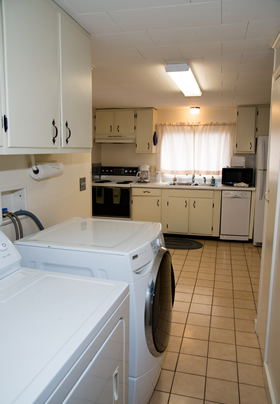 Large white kitchen with white washer and dryer in a house.