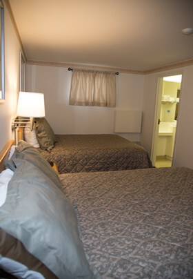 Room with two double beds with small tan curtains and wall lamps.