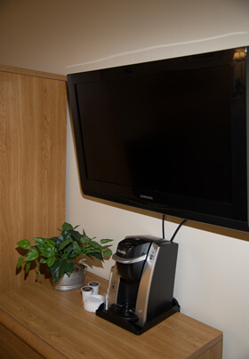 Large flat screen TV with black coffee maker on a wooden stand.