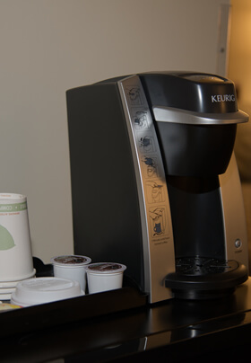 Black coffee making machine with coffee pods, green bedding in background.